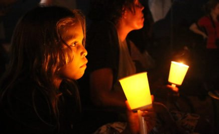An Aboriginal girl holds a lantern in the dark, another girl sits beside her