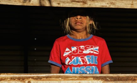 Aboriginal girl looking through old window, wearing a red t-shirt with 'Aussie' on it. Broome, Western Australia.