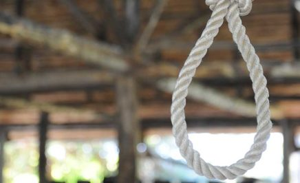 Loop of rope hanging on a wooden background