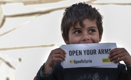 A young boy holding a Open to Syria campaign sign