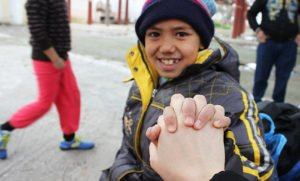 Young refugee boy holding someone's hand