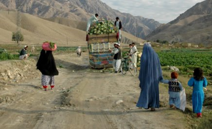 A woman and her family walking behind a cart in rural Afghanistan