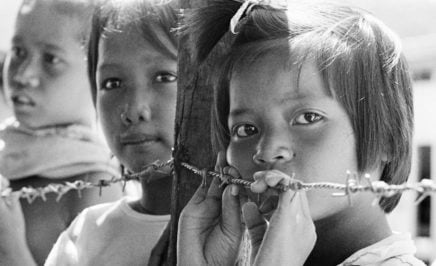 Three young refugees children leaning against barbed wire in South East Asia
