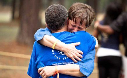 Two people hug at a vigil in Jackson