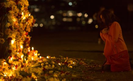 A person kneels in prayer at a #keephopealive vigil in Sydney to end the death penalty