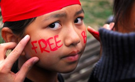 A young girl with 'Free Burma' written across her cheeks