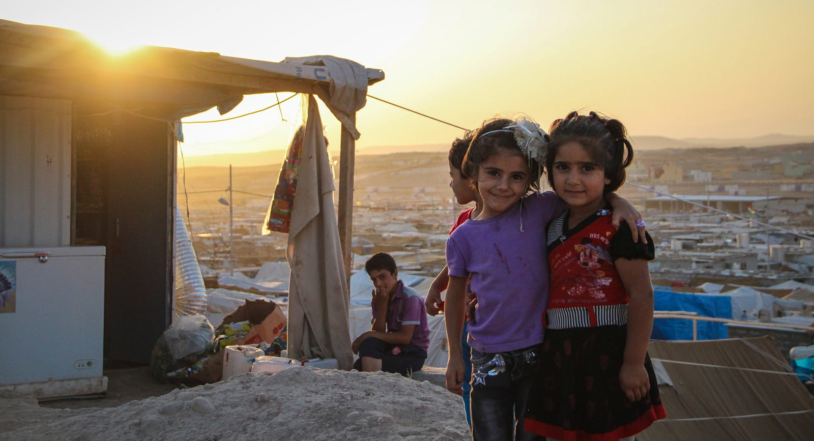 Two young girls in a refugee camp at sunset