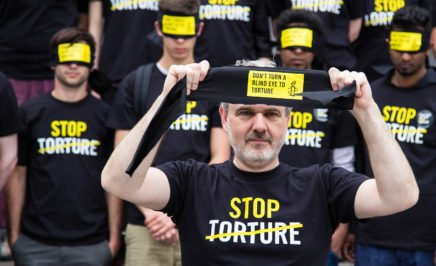 Amnesty protesters with Stop Torture T-shirts and blindfolds at a rally.