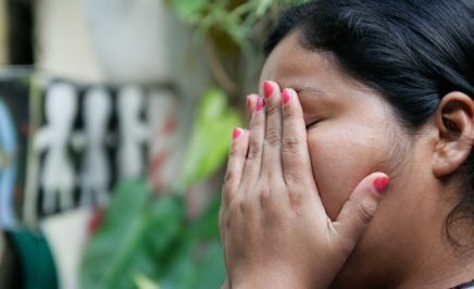 Woman with her hands over her face. Marlene, was accused and charged with having an abortion after she had a miscarriage when she was 18 years old.