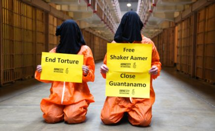 two people in Guantanamo Bay style orange jumpsuits - one holding a sign that says End Torture; the other holding a sign which says that says Free Shaker Aamer and Close Guantanamo.