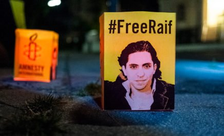 A small sign that reads '#FreeRaif' at a vigil outside the Saudi Arabian embassy in Vienna