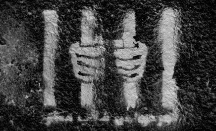 White graffiti of hands behind bars on a black wall