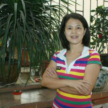 Chinese women's rights activist Su Changlan smiles into the camera with arms crossed