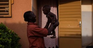 A woman plays with her child outside a shelter in Burkina Faso, which has the 7th highest rate of child marriage in the world.