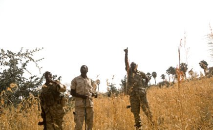 Two military chaplains and a soldier point to the sky as an airplane passes overhead in Sudan
