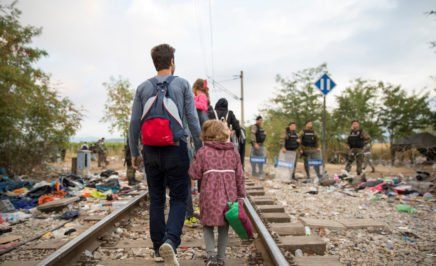 Refugees and migrants cross the border from Greece into Macedonia, A man with a backpack walks with a little girl along a train track.