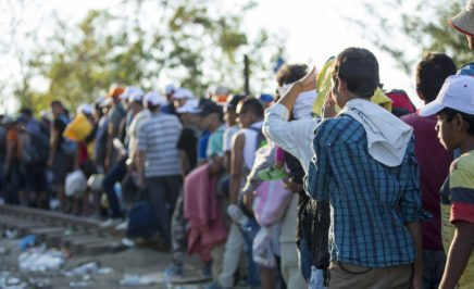 A long line of refugees, many holding personal possessions, waiting at the Greece-Macedonian border.