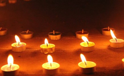 Close-up of some small lit candles lined up in a row.