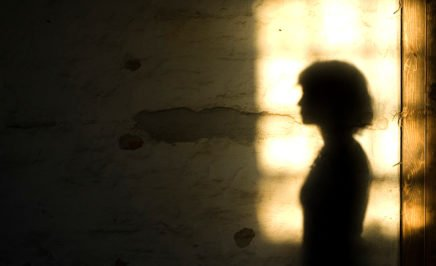A woman's silhouetted shadow against a wall