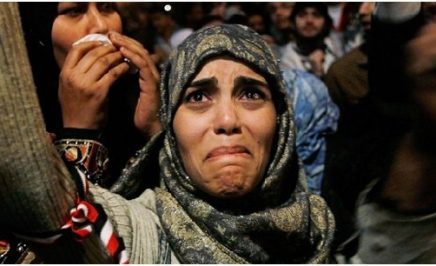 A woman cries at a protest with her arms raised in Tahrir Square after it is announced that Egyptian President Hosni Mubarak was giving up power. Tahrir Square, Egypt, 2011.