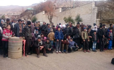 Syrians wait for the arrival of an aid convoy on January 11, 2016 in the besieged town of Madaya.