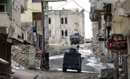 Military vehicles move a deserted street in southerneastern Turkey following clashes between Turkish forces and Kurdish militants on November 10, 2015.