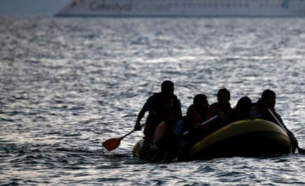 Migrants arrive on the shore of Kos island on a small dinghy.