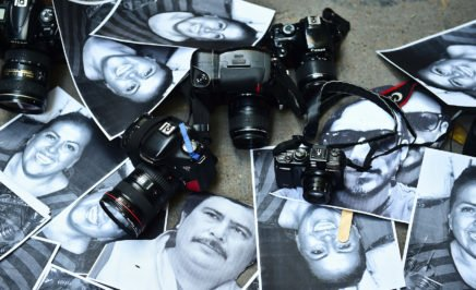 Photos of killed journalists with cameras at a protest for press freedom in Mexico City