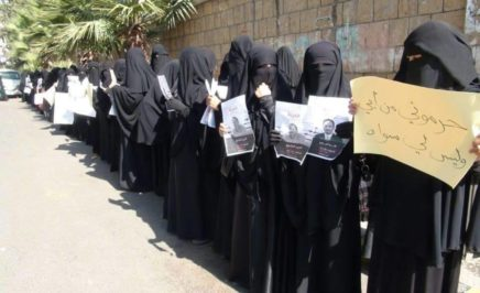 Women wearing black niqab stand in front of a wall holding protest signs in Arabic