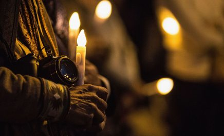 An activist holds a camera and a candle at a vigil