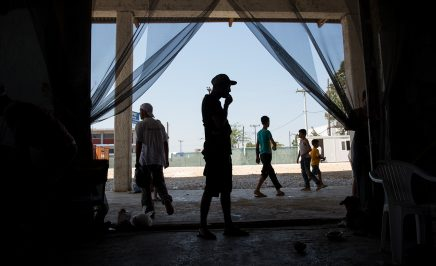 Men stand ouside and under a concrete roof at the Softex refugee camp in Sindos, near Thessaloniki.