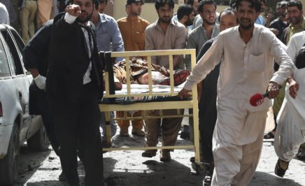 Pakistani lawyers and local media personnel carry a bed to move the body of a news cameraman after a bomb explosion at a government hospital in Quetta.