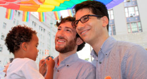 Two men standing together, smiling and holding a young child under a rainbow flag.