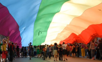 A large group of people standing under a rainbow flag.