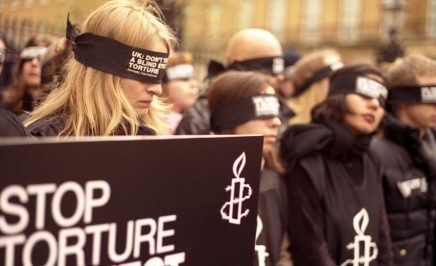 Activists at UK rally wearing 'Stope torture' shirts and blindfolds over their eyes.
