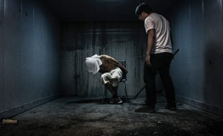 Staged photo of a man being tortured in a dark room
