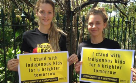 Two activists hold placards declaring that they stand with Indigenous kids for a brighter tomorrow