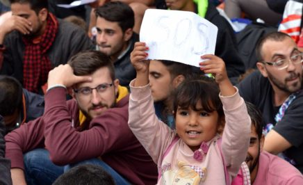child holds up a sign with SOS written on it, while standing in a crowd of people