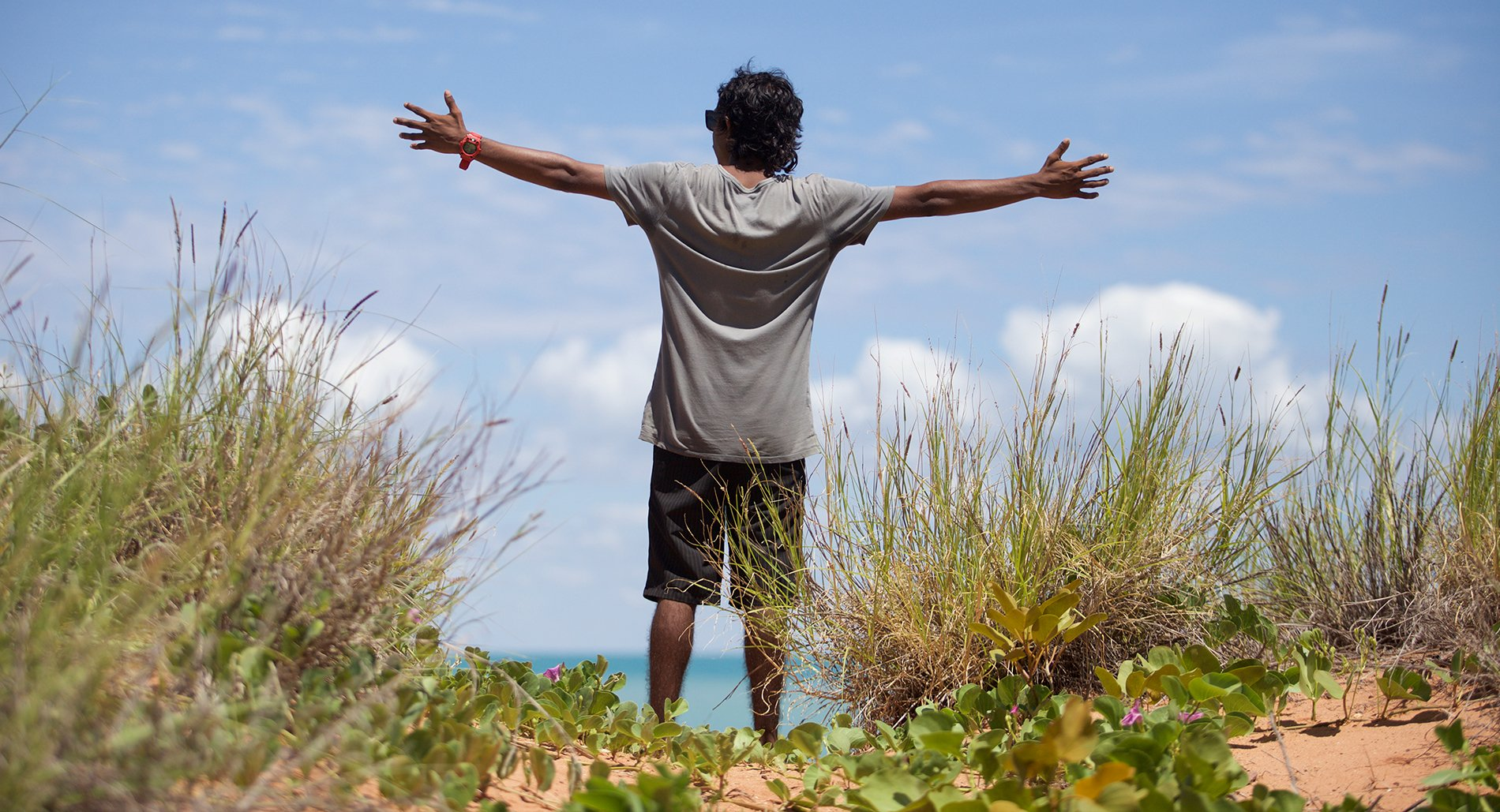 A young Indigenous man with his arms outstretched toward the ocean