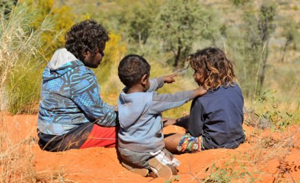 Three young Indigenous people sitting on red outback sand.