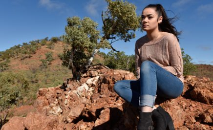 Justice King, a young Indigenous advocate, sits on an escarpment of orange rock