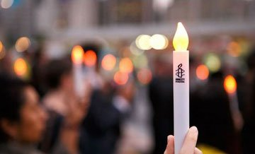 Close up of an Amnesty candle at a vigil