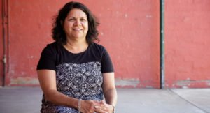 Glenda Joyce Kickett, a Noongar woman from Perth standing in front of a red wall