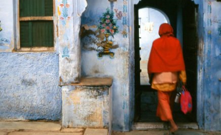 A person dressed in red walking through a blue doorway in India