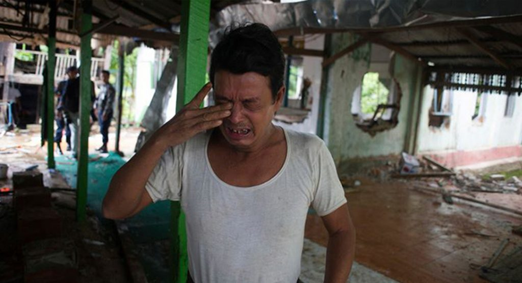 A man cries after a mosque is burned down in Myanmar
