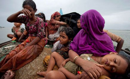 Group of Rohingya refugee women and children on boat at sea