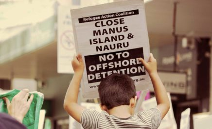 Boy holds a close Manus and Nauru sign