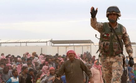 A Jordanian soldier stands guard as Syrian refugees arrive to a camp