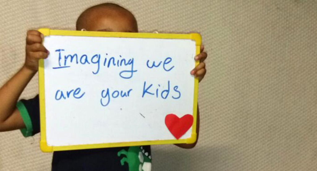 "A child in the Refugee Processing Centre on Nauru holds sign that reads ""Imaging we are your kids"". © Private"