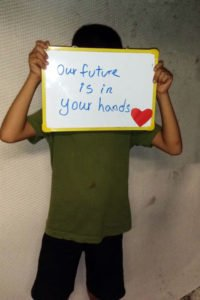 A child in the Refugee Processing Centre on Nauru holding a sign appealing for support. © Private